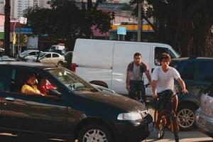 """Segunda, 5 de abril: jovens atravessam a Avenida Sumaré """"costurando"""" entre os carros parados no sinal vermelho. por Mario Rodrigues"""